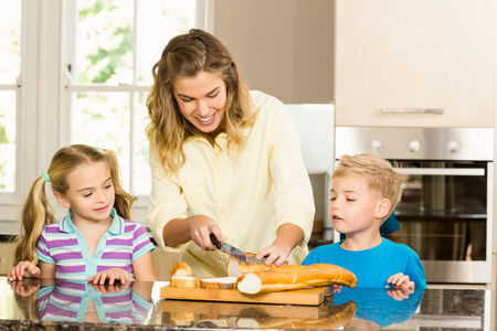 comiendo pan: pan rebanado feliz familia en la cocina Foto de archivo