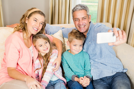 family sofa: Happy family taking selfie on the sofa in living room Stock Photo