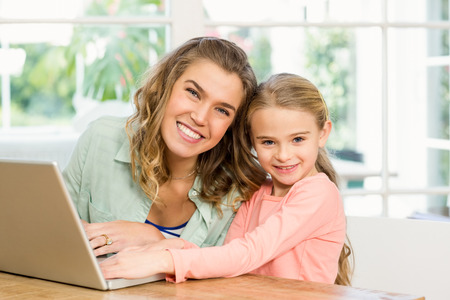 daugther: Mother and daughter using laptop together
