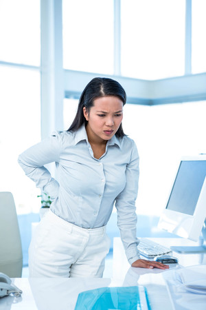 back ache: Frowning businesswoman with back ache standing in office