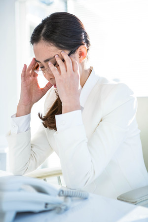 wincing: Stressed businesswoman working at her desk in work Stock Photo