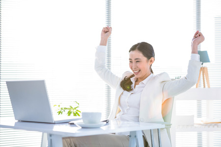 Businesswoman rejoicing with arms outstretched in office