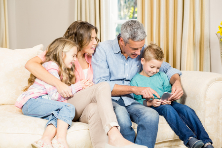 family sofa: happy family using phone on sofa in the living room Stock Photo