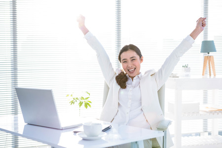 happy asian people: Businesswoman rejoicing with arms outstretched in office