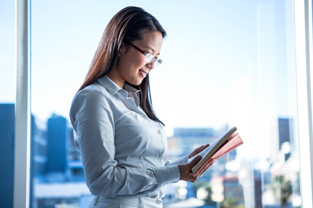 well read: Smiling businesswoman reading book in office near the window