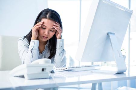 unsmiling: Unsmiling businesswoman with hands on head in office