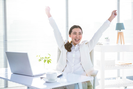 rejoicing: Businesswoman rejoicing with arms outstretched in office