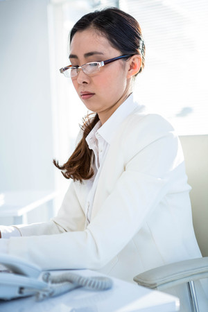 at her desk: Serious businesswoman working at her desk in her office Stock Photo
