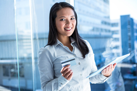 Smiling businesswoman holding laptop and credit card in office near the window Stock Photo