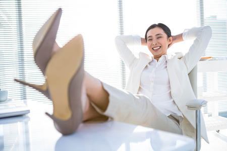 feet on desk: Relaxed businesswoman sitting with her feet up at desk Stock Photo