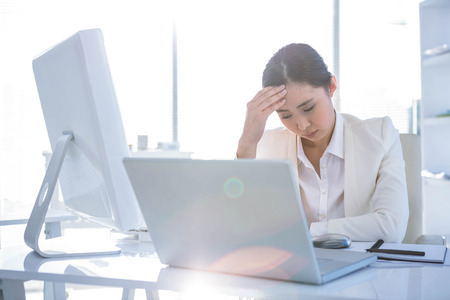 pounding head: Stressed businesswoman working at her desk in work Stock Photo