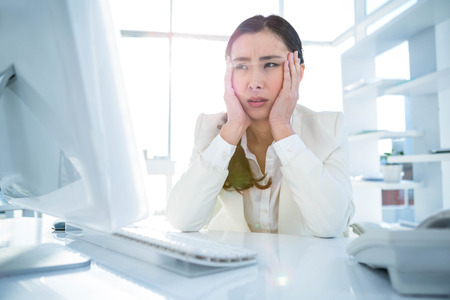 Stressed businesswoman working at her desk in work Stock Photo