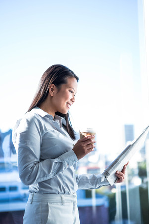 Smiling businesswoman holding disposable cup reading newspaper in office near the window Stock Photo