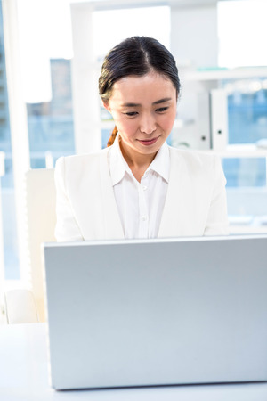 chinese adult: Smiling businesswoman with laptop working at her desk