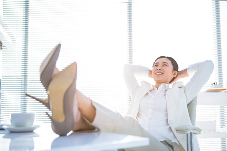feet up: Relaxed businesswoman sitting with her feet up at desk Stock Photo