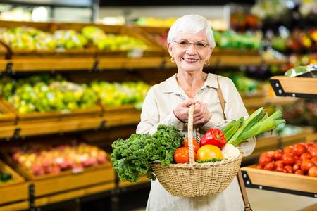 Senior vrouw met rieten mand in de supermarkt