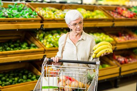 年配の女性がスーパー マーケットで彼女のトロリーにバナナを入れて