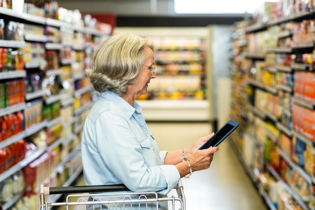 retail shopping: Smiling senior woman with cart using tablet in the supermarket Stock Photo