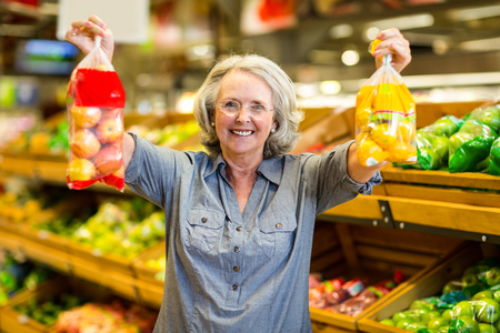 woman holding bag: Senior happy woman holding bag of fruits in supermarket Stock Photo
