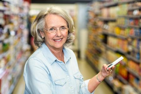 Smiling senior woman using smartphone at the supermarket