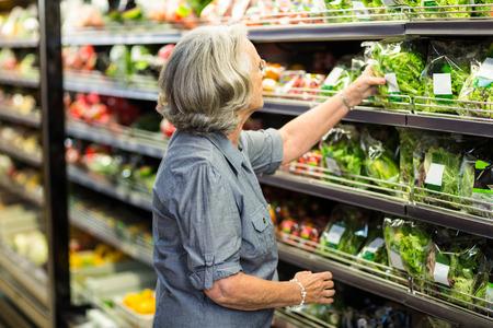 vegetables supermarket: Senior woman picking out some vegetables in supermarket