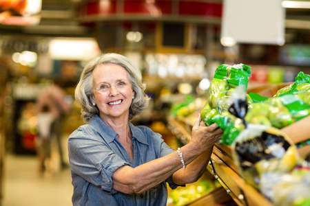 woman holding bag: Senior happy woman holding bag of salad in supermarket