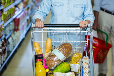 mid section: Mid section of smiling senior woman pushing cart at the supermarket