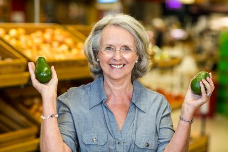 food woman: Senior woman holding two avocado in supermarket Stock Photo