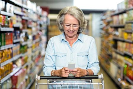 woman shopping cart: Smiling senior woman using smartphone at the supermarket Stock Photo