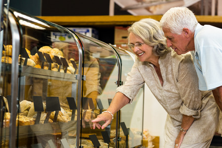 bakery store: Senior couple pointing puddings at the bakery store