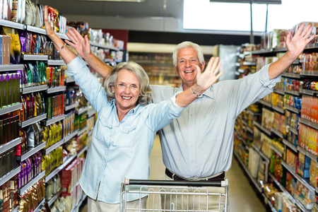 woman shopping cart: Happy senior couple at the supermarket raising arms
