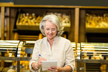 bakery store: Smiling senior woman checking list at the bakery store Stock Photo