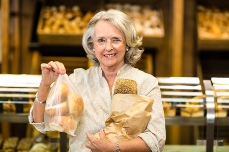 bakery store: Smiling senior woman holding bags with bread at the bakery store