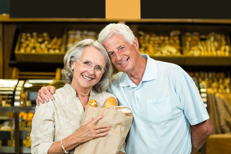 bakery store: Smiling senior couple holding bakery bag at the bakery store