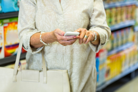 mid section: Mid section of woman using smartphone at the supermarket