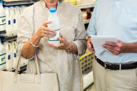 mid section: Mid section of senior couple buying milk and checking list at the supermarket Stock Photo