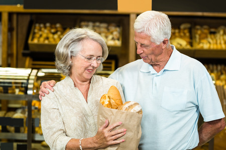 bakery store: Senior couple holding bakery bag at the bakery store Stock Photo