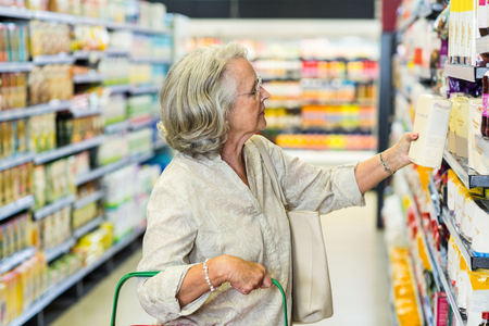 food products: Senior woman buying food at the supermarket Stock Photo