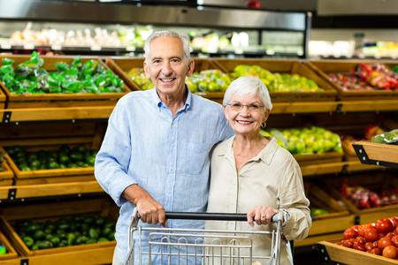 abarrotes: Pares mayores felices con la compra en la tienda de comestibles Foto de archivo