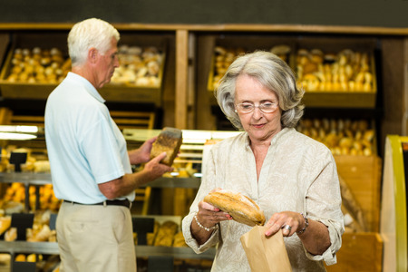 bakery store: Senior couple buying bread at the bakery store