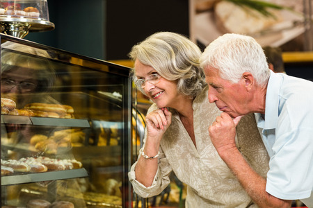 bakery store: Senior couple looking puddings at the bakery store