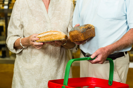 mid section: Mid section of senior couple buying bread at the bakery store Stock Photo