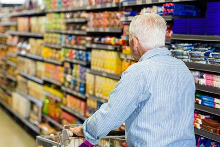 man pushing: Rear view of senior man pushing trolley in supermarket Stock Photo