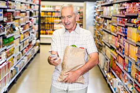 grocery bag: Senior man with grocery bag using smartphone at the supermarket Stock Photo