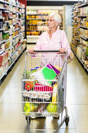 empujando: Concentrado mujer mayor que empuja carrito de supermercado