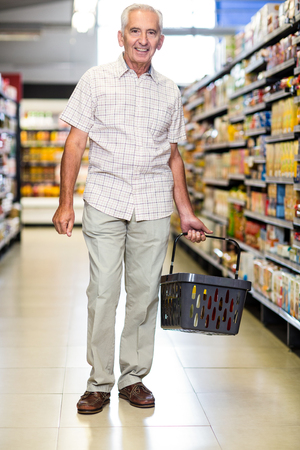 Smiling senior man holding basket in supermarket Stock Photo