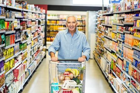man pushing: Smiling senior man pushing trolley in supermarket