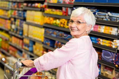 empujando: Mujer mayor que empuja la compra en el supermercado sonriendo