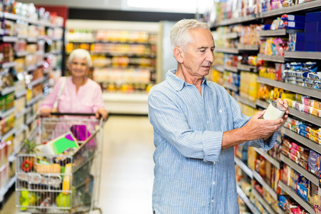 Senior man looking at canned food in supermarket
