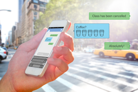 text messaging: hand holding smartphone against smartphone text messaging Stock Photo